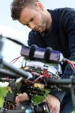 Technician Fixing Camera On UAV Drone. Closeup of young technician fixing camera on UAV drone in park stock images
