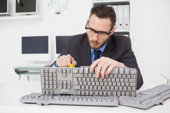 Technician fixing keyboard with screw driver Stock Images