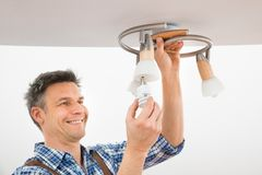 Technician fixing light on ceiling. Portrait Of A Male Electrician Fixing Light On Ceiling Royalty Free Stock Photography