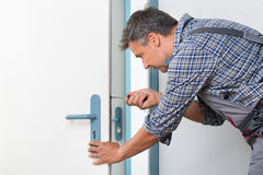 Technician Fixing Lock In Door With Screwdriver. Cropped image of technician fixing lock in door with screwdriver at home Stock Photo