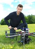 Technician Fixing Propeller Of UAV Octocopter. Portrait of confident young technician fixing propeller of UAV octocopter in park royalty free stock photos