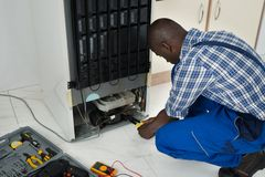 Technician Fixing Refrigerator With Worktool. Young African Technician Fixing Refrigerator With Worktool Stock Image