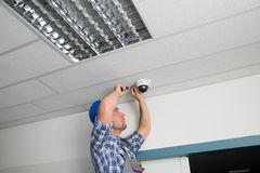 Technician fixing security camera. Close-up Of Male Technician Adjusting Cctv Camera On Ceiling Stock Photos
