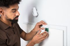 Technician Fixing Security System Door Sensor. Close-up Of A Young Male Technician`s Fixing Security System Door Sensor stock photo