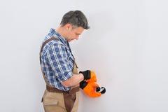 Technician fixing socket on wall Stock Photography