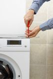 Technician fixing washing machine with screwdriver Royalty Free Stock Photo