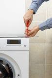 Technician fixing washing machine with screwdriver Royalty Free Stock Photo