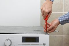 Technician fixing washing machine with screwdriver Stock Images