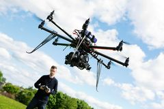 Technician Flying UAV Helicopter in Park. Young technician flying UAV drone with remote control in park Stock Photography