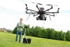 Technician Flying UAV Octocopter in Park. Happy young male technician flying UAV octocopter with remote control in park Royalty Free Stock Photos