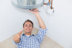 Technician gesturing thumbs up by hot water heater Stock Images