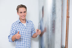 Technician gesturing thumbs up by hot water heater Stock Image