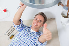 Technician gesturing thumbs up by hot water heater Royalty Free Stock Images