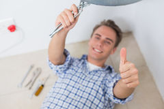 Technician gesturing thumbs up under hot water heater Stock Photo