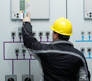 Technician  give command in power plant control center. Engineer in yellow helmet give command in power plant control center Royalty Free Stock Image