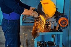 Technician in gloves and overalls in the workplace. Cutting metal with a machine in the shop. Photos of the work process stock photo