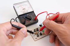 Technician hand with multimeter probes repairing circuit board stock image