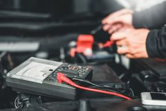 Technician Hands of car mechanic working in auto repair Service and Maintenance car battery.  stock photography