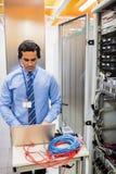 Technician in head phones using laptop. In server room Royalty Free Stock Image
