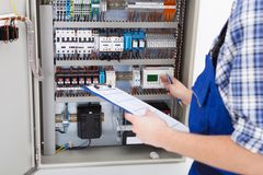 Technician holding clipboard while examining fusebox. Cropped image of male technician holding clipboard while examining fusebox Royalty Free Stock Images