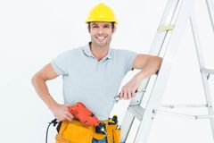 Technician holding drill machine while leaning on step ladder. Portrait of confident technician holding drill machine while leaning on step ladder Stock Photography