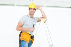 Technician holding hammer while wearing hard hat on step ladder Stock Image