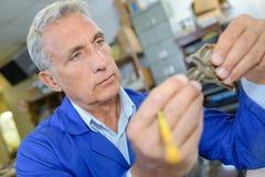 Technician holding mechanical part Stock Photo