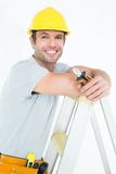 Technician holding pliers while leaning on step ladder Royalty Free Stock Photos