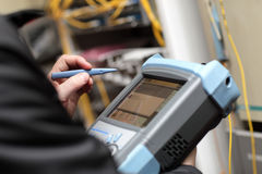 Technician holding reflectometer. The technician holding a optical reflectometer at server room Royalty Free Stock Photo