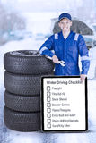 Technician with information about winter driving. Young technician leaning with a stack of tires while holding wrench and information about winter driving on the Stock Photos