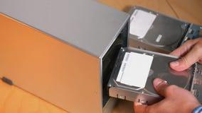 IT Technician Inserts Hard Drives into External RAID Array. An IT computer technician inserts five hard drives into an external desktop RAID array stock footage