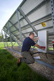 Technician inspecting control panel on large solar panel Royalty Free Stock Image