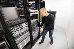 IT Technician Installing Blade Server In Chassis At Datacenter. High angle view of IT technician installing blade server in chassis at datacenter Stock Photo