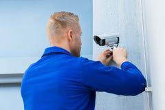 Technician Installing Camera In Corner. Close-up Of A Young Technician Installing Camera In Building Corner Stock Photos