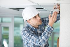 Technician installing camera on wall with screwdriver. Installing Royalty Free Stock Photo