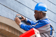 Technician Installing Camera On Wall. Young Male Technician Installing Camera On Wall Stock Image