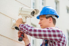 Technician Installing Camera On Wall. Young Male Technician Installing Camera On Wall With Screwdriver Royalty Free Stock Photos