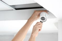 Technician installing CCTV camera. On ceiling indoors, closeup Royalty Free Stock Photo