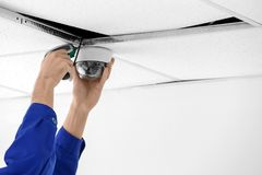 Technician installing CCTV camera. On ceiling indoors, closeup Stock Image