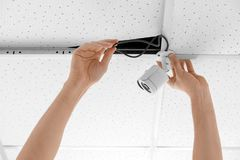 Technician installing CCTV camera on ceiling indoors. Closeup Stock Photography
