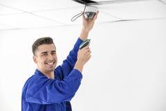Technician installing CCTV camera on ceiling indoors. Professional technician installing CCTV camera on ceiling indoors Stock Photo