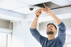 Technician installing CCTV camera. On ceiling indoors Stock Photography