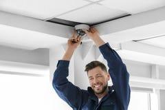 Technician installing CCTV camera. On ceiling indoors Stock Photo