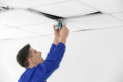 Technician installing CCTV camera. On ceiling indoors Stock Image