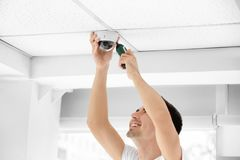 Technician installing CCTV camera. On ceiling indoors Royalty Free Stock Photos