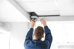 Technician installing CCTV camera on ceiling. Indoors Stock Photos