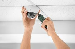 Technician installing CCTV camera on ceiling indoors. Closeup Royalty Free Stock Photo