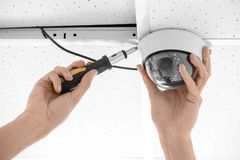 Technician installing CCTV camera on ceiling indoors. Closeup Royalty Free Stock Images