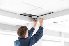 Technician installing CCTV camera. On ceiling indoors stock photo