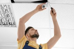 Technician installing CCTV camera. On ceiling indoors Royalty Free Stock Photo
